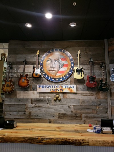 Presidential Pawn sign surrounded by electric guitars.
